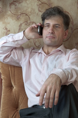 Portrait of middle-aged men talking on the telephone at home Stock Photo - 12321851