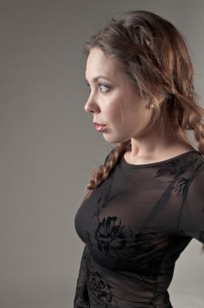 Retrato de una joven y bella chica en una ropa de color oscuro