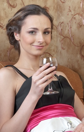 Portrait of a young and beautiful girl with a glass of red wine photo