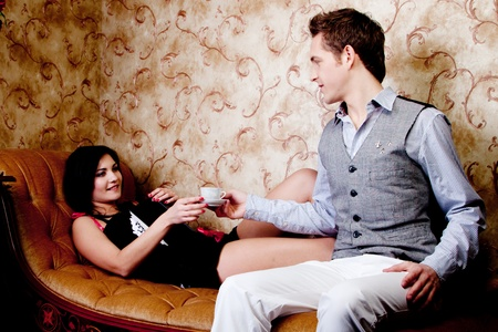 The young and handsome man gives coffee a charming young girl, which lies on the sofa decorated against the wall with wallpaper decorated withornaments Stock Photo - 12599940