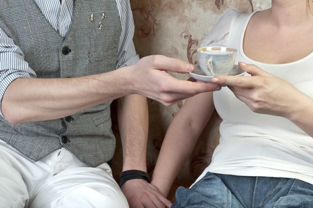 The young and handsome man gives coffee a charming young girl, which lies on the sofa decorated against the wall with wallpaper decorated withornaments Stock Photo - 12599947