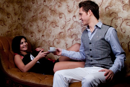 The young and handsome man gives coffee a charming young girl, which lies on the sofa decorated against the wall with wallpaper decorated withornaments Stock Photo - 12599925
