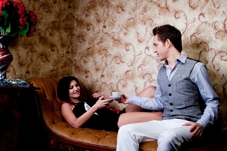 The young and handsome man gives coffee a charming young girl, which lies on the sofa decorated against the wall with wallpaper decorated withornaments Stock Photo - 12599916