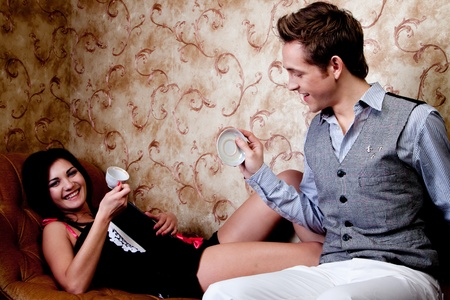 The young and handsome man gives coffee a charming young girl, which lies on the sofa decorated against the wall with wallpaper decorated withornaments Stock Photo - 12599979