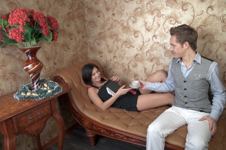 The young and handsome man gives coffee a charming young girl, which lies on the sofa decorated against the wall with wallpaper decorated withornaments Stock Photo - 12599899