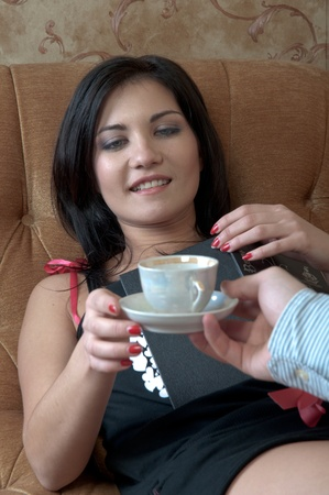 The young and handsome man gives coffee a charming young girl, which lies on the sofa decorated against the wall with wallpaper decorated withornaments Stock Photo - 12599919