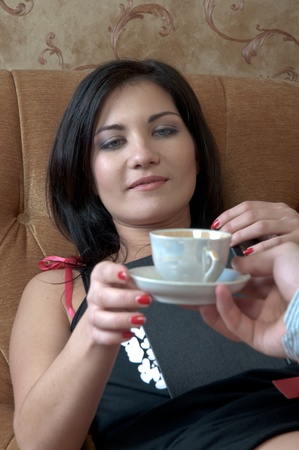 The young and handsome man gives coffee a charming young girl, which lies on the sofa decorated against the wall with wallpaper decorated withornaments photo