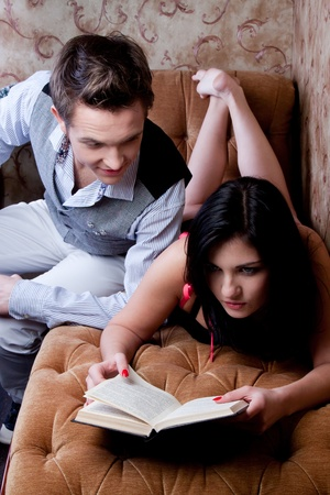 Young and beautiful couple reading a book while sitting on the couch in the roomdecorative wallpaper decorated with patterns Stock Photo - 12600259
