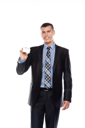 Portrait of a businessman in a business suit with a white business card in his hand photo