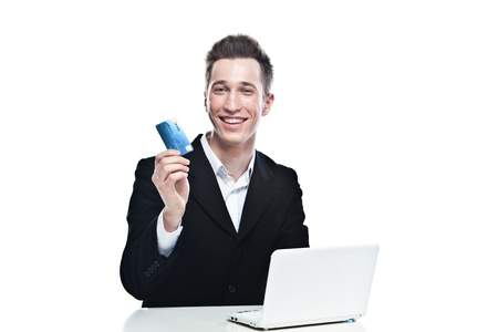 portrait of a young handsome man in the strict business suit shopping via the Internetusing a credit card and laptop Stock Photo - 12598931