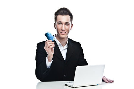 portrait of a young handsome man in the strict business suit shopping via the Internetusing a credit card and laptop Stock Photo - 12598932