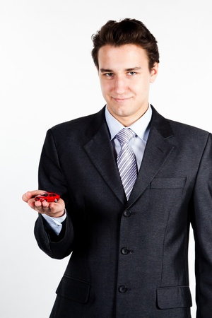 portrait of a young manager for motor with a small red toy car photo
