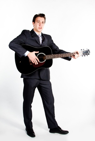 Young handsome man in a dark business suit, sings and plays guitar Stock Photo