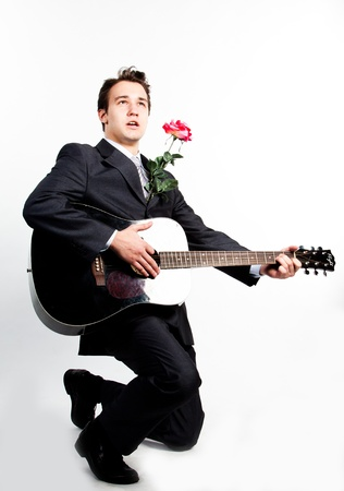 Young handsome man in a dark business suit, sings and plays guitar photo