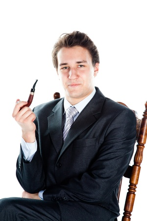 pipe smoking: Portrait of a young handsome man in a dark suit with a strict smoking a pipe in his hand Stock Photo