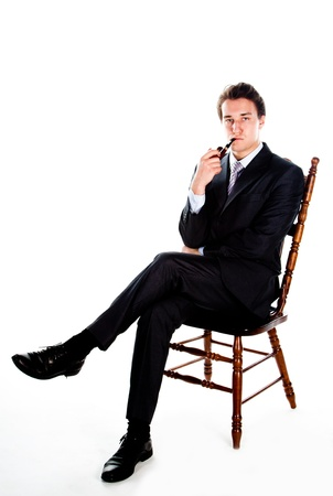 Portrait of a young handsome man in a dark suit with a strict smoking a pipe in his hand photo