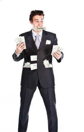 Portrait of a young businessman in a dark suit surrounded by flying dollar bills photo
