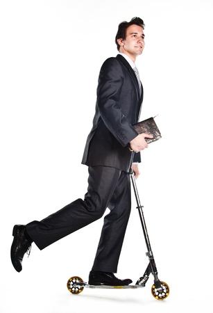 Portrait eines jungen seriöser und erfolgreicher Mann in einem dunklen Anzug, der einen Roller reitet