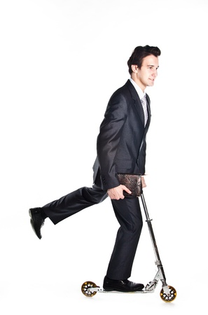 Portrait of a young respectable and successful man in a dark business suit who rides a scooter photo