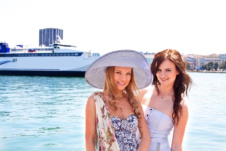Portrait of two young and beautiful girls in the background of a large ocean liner photo