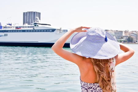 Portrait of a young and beautiful girl in the background of a large ocean liner photo