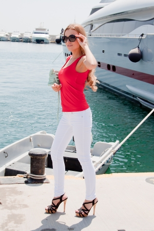 Photo of a young and beautiful girl against the backdrop of yachts in the port Stock Photo - 13659051