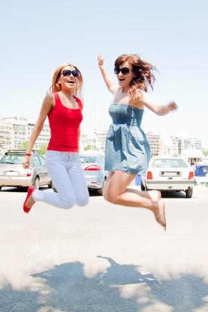 Photo of a young, beautiful and cheerful girl who jumps high sunny summer day photo