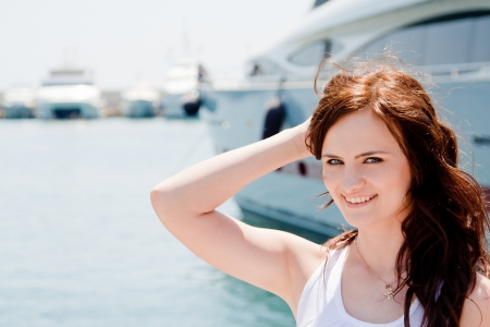 Photo of a young and beautiful girl against the backdrop of yachts in the port photo