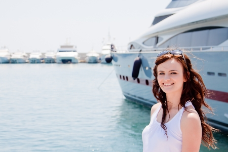 Photo of a young and beautiful girl against the backdrop of yachts in the port