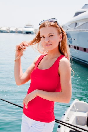 Photo of a young and beautiful girl against the backdrop of yachts in the port Stock Photo - 13777325