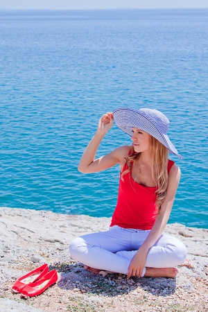 Young and beautiful girl resting on rocks against the sea Stock Photo - 13764930