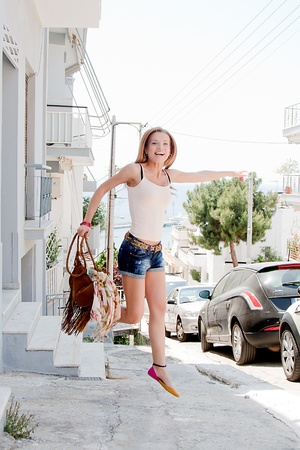 Photo of a young and beautiful girl walking down the street photo
