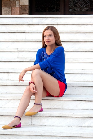 young and beautiful woman sitting on the steps of Stock Photo
