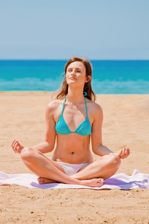 young and beautiful woman who practices yoga on the beach photo