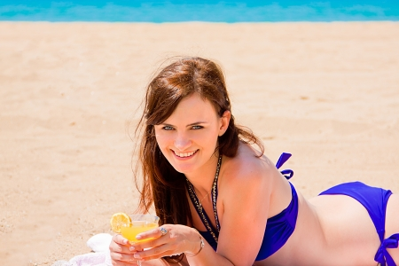 young and beautiful woman who is resting on the beach and drink a drink from a glass photo
