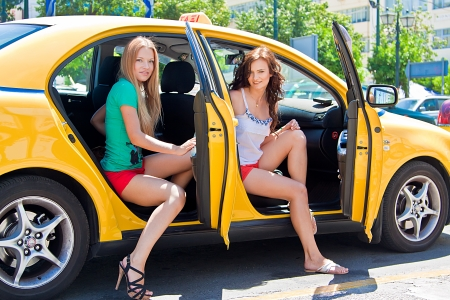 Photo of two young and beautiful women in the taxi Stock Photo