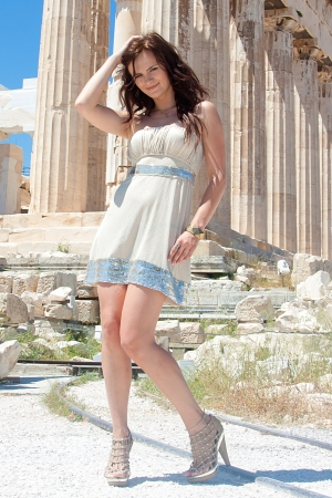 Photo of a young and beautiful woman on the background of the ancient Acropolis photo