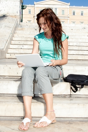 young and beautiful woman sitting on the steps of photo