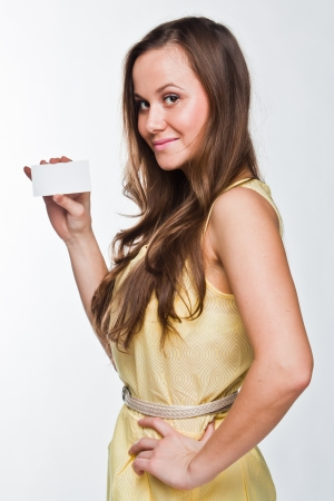 Photo of a young and beautiful woman with a business card in the hands of photo