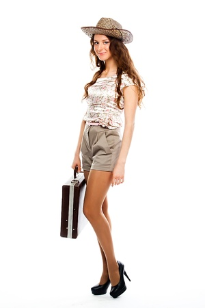 Photo of a young and beautiful girl with a suitcase, passport and ticket isolated on white background photo