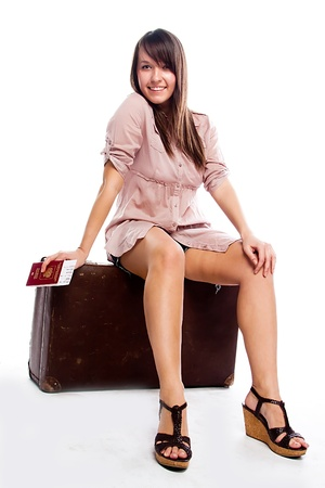 Photo of a young and beautiful girl with a suitcase, passport and ticket isolated on white background Stock Photo - 14227204