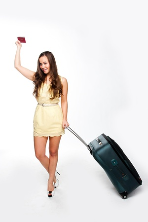 Photo of a young and beautiful girl with a suitcase, passport and ticket isolated on white background Stock Photo - 14227076