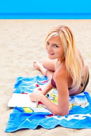 A young and beautiful woman resting on a beach reading a book in hard cover green photo