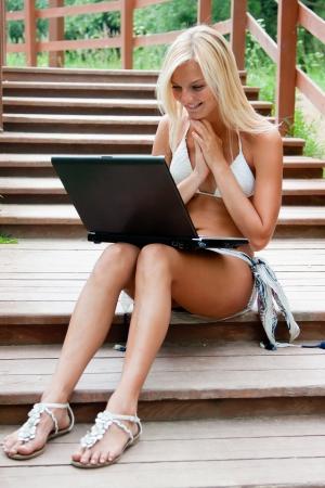 net surfing: Giovane e bella donna con un computer portatile per le scale nel parco