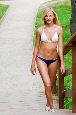 20 25: A beautiful young woman in a bathing suit climbing the stairs in the park