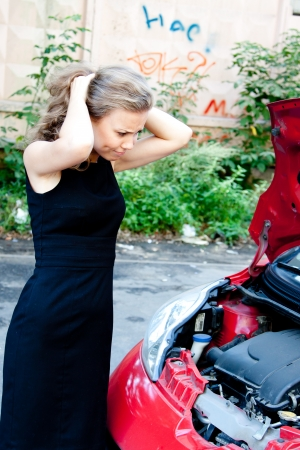 Beautiful young woman near the broken car photo
