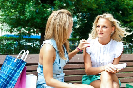 Two beautiful young woman resting on a bench in the park after shopping Stock Photo