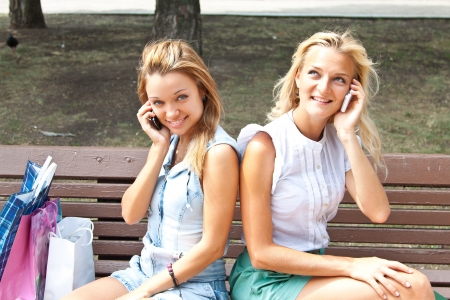 Two beautiful young women talking on the phone while sitting on a park bench Stock Photo - 15384470