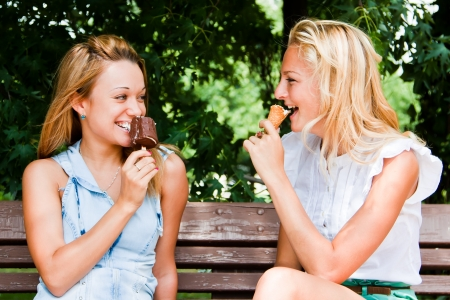 Two young and beautiful woman eating ice cream on a bench in the park photo