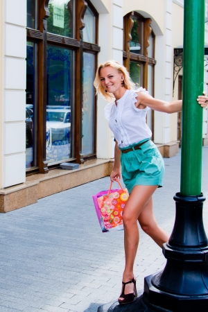 Young and beautiful woman walking down the street with shopping bags in photo